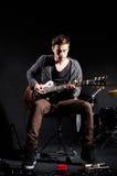 Man som spelar gitarren i mörkt rum Arkivfoto