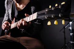 Man som spelar gitarren i mörkt rum Royaltyfri Foto