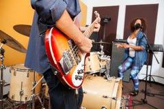 Man som spelar gitarren medan kvinna som sjunger och dansar Fotografering för Bildbyråer