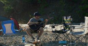 Man som spelar gitarren nära flodstranden 4k arkivfilmer