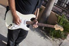 Man som spelar gitarren på strandpromenad Royaltyfri Foto