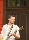 Man som spelar gitarren under en utomhus- konsert Arkivbild