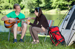 Man som spelar gitarrsången för kvinna Arkivfoto