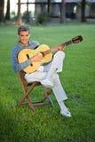 Man som spelar gitarrsammanträde i gräsmatta Arkivfoto