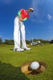 Man som spelar golf mot blå himmel Arkivfoto