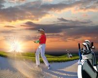 Man som spelar golf mot solnedgång royaltyfri bild