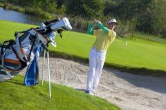 Man som spelar golf under solig dag Arkivfoto