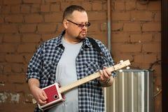 Man som spelar hans gitarr för cigarrask Royaltyfri Fotografi