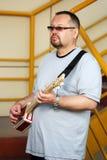 Man som spelar hans gitarr för cigarrask Royaltyfria Foton