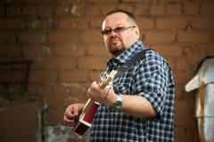 Man som spelar hans gitarr för cigarrask Arkivbilder