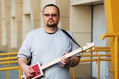 Man som spelar hans gitarr för cigarrask Royaltyfria Bilder