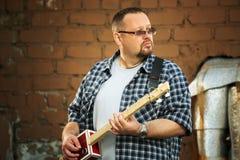 Man som spelar hans gitarr för cigarrask Arkivfoto