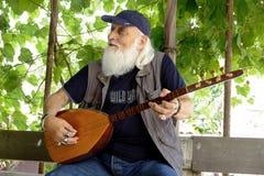 Man som spelar hans handgjorda Baglama arkivfoto
