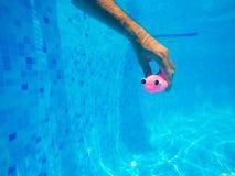 Man som spelar med den generiska rubber fiskleksaken i simbassäng Royaltyfria Foton