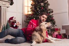 Man som spelar med hunden på christmastime royaltyfria foton