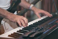 Man som spelar pianot på dramatisk mörk etapp på suddig bakgrund för gitarrspelare fotografering för bildbyråer