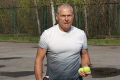 Man som spelar tennis p? den utomhus- domstolen royaltyfri foto
