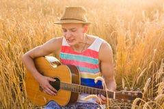 Man som spelar utomhus den akustiska gitarren Royaltyfria Bilder