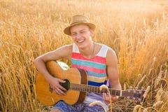 Man som spelar utomhus den akustiska gitarren Fotografering för Bildbyråer