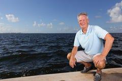 Man som squatting vid skyddsmuren mot havet Arkivfoton