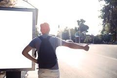 Man som står den near hållplatsen som tummar en elevator Arkivfoto