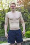 Man som står shirtless det fria i en parkera arkivbild