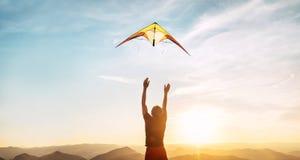 Man som startar att flyga den ljusa draken i solnedgånghimmel över det höga berget Lyckad startbegreppsbild royaltyfri foto