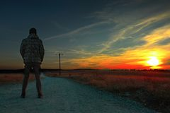 Man som stirrar på solnedgången royaltyfri foto