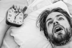 Man som str?cker i s?ng Elasticitet efter vak upp i morgonen Attraktiv ung man som kopplar av p? s?ng fotografering för bildbyråer