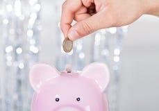 Man som sätter in myntet i Piggybank Arkivbild
