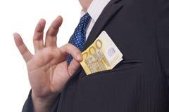 Man som sätter pengar i hans fick- Royaltyfria Bilder