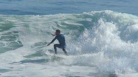 Man som surfar en våg i Kalifornien i ultrarapid lager videofilmer