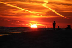 Man som surfcasting i solnedgången i Alabama Arkivbild