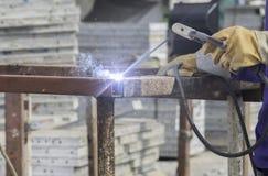 Man som svetsar en stålplatta som fästas till stålasken Arkivbilder