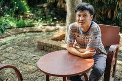 Man som svettas sammanträde på den wood stolen på trädgården royaltyfri foto