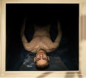 Man som svävar i en sensorisk förlustisoleringsbehållare Arkivbilder