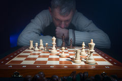 Man som tänker bak schackbrädet Arkivbild