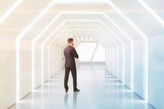 Man som tänker i futuristisk vit korridor arkivfoton