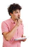 Man som tänker med en blyertspenna och en anteckningsbok Fotografering för Bildbyråer