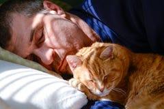 Man som ta sig en tupplur med katten Royaltyfria Bilder