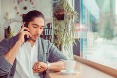 Man som talar av den smarta telefonen som ser armbandsuret som kontrollerar tid royaltyfri bild