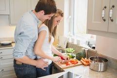 Man som talar med kvinnan, medan laga mat Arkivfoto
