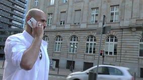 Man som talar med mobiltelefonen i stad och affärstorn arkivfilmer