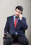 Man som talar på den retro telefonen Arkivfoto