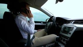 Man som talar på mobiltelefonen i bil stock video