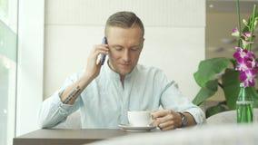 Man som talar på smartphonen och dricker kaffe arkivfilmer