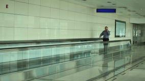 Man som talar på telefonen som går till och med flygplats stock video
