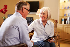 Man som talar till den kvinnliga rådgivaren som använder den Digital fliken royaltyfria bilder