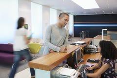 Man som talar till receptionisten At Office Royaltyfri Bild