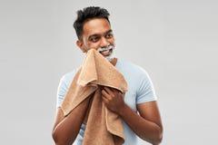 Man som tar bort raka skum från framsida vid handduken arkivfoton